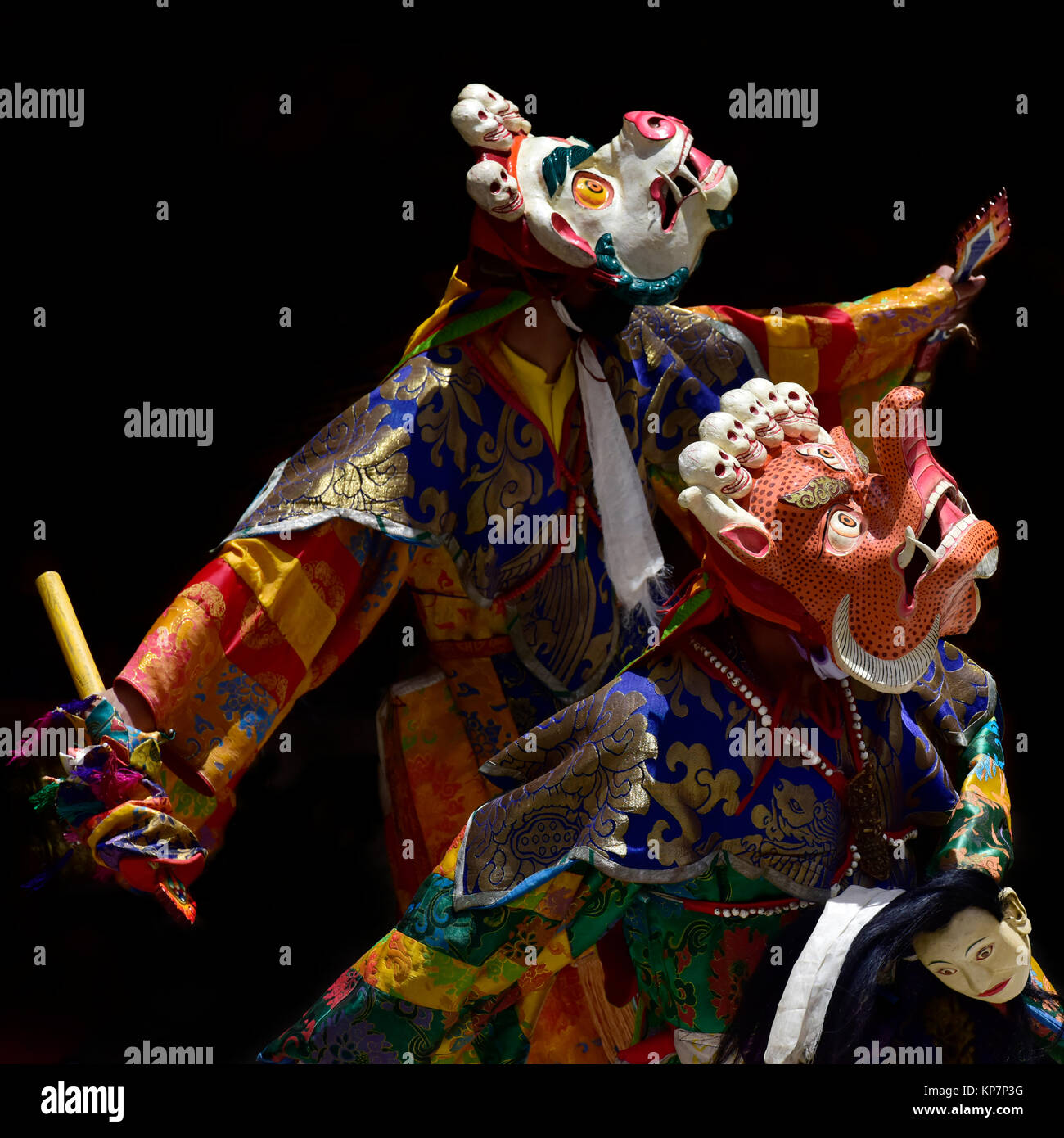 Buddhist monks in ritual national Tibetan clothes perform the Mask Dance depicting human sacrifice. Stock Photo
