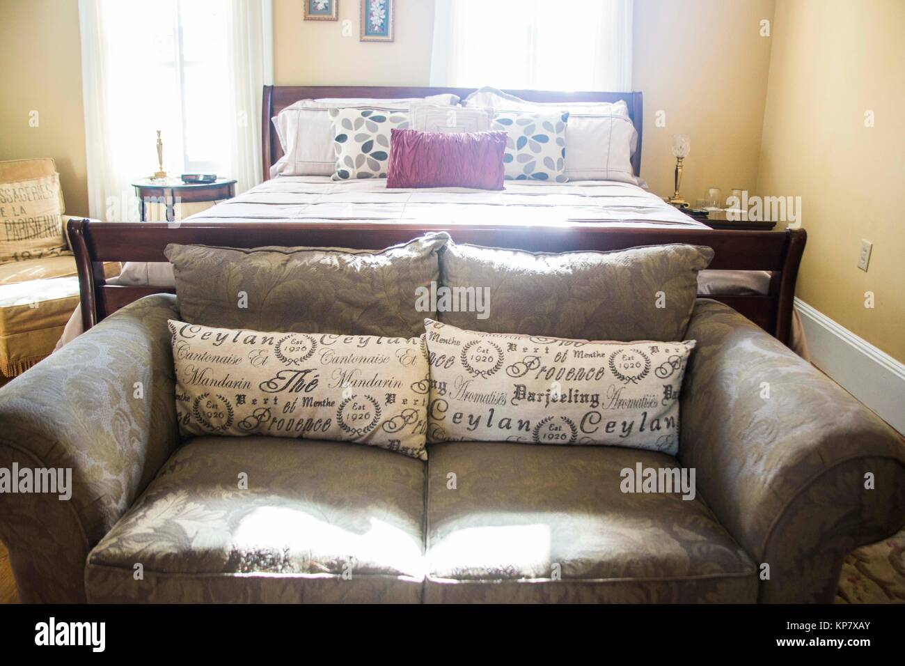Inside the bedroom of a bed and breakfast. We can see a gorgeous coach adorned with plush pillows, to be used by - Stock Image