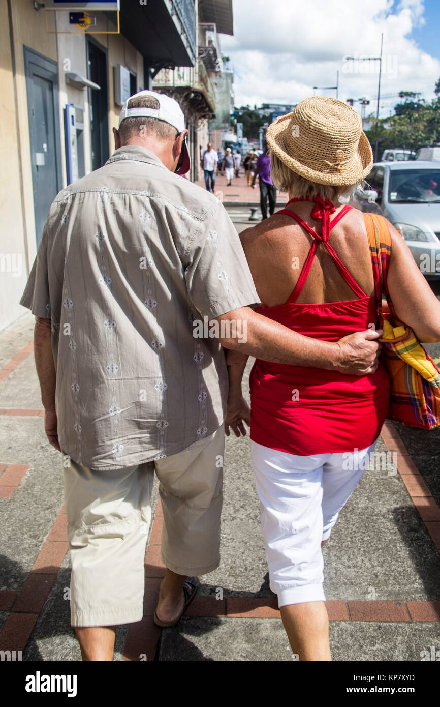 Older mature couple holding each other back, being in love, while strolling the streets of Fort De France. - Stock Image