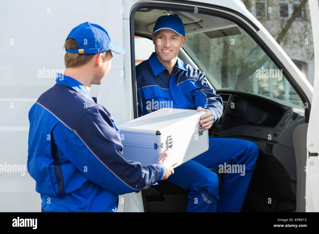 Happy Technician Giving Toolbox To Colleague - Stock Image