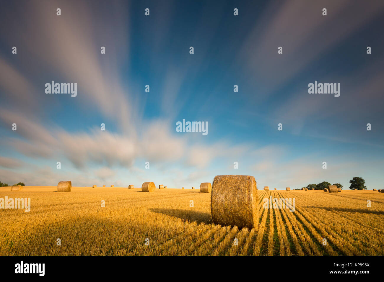 drawing clouds on field with straw bales,long exposure Stock Photo