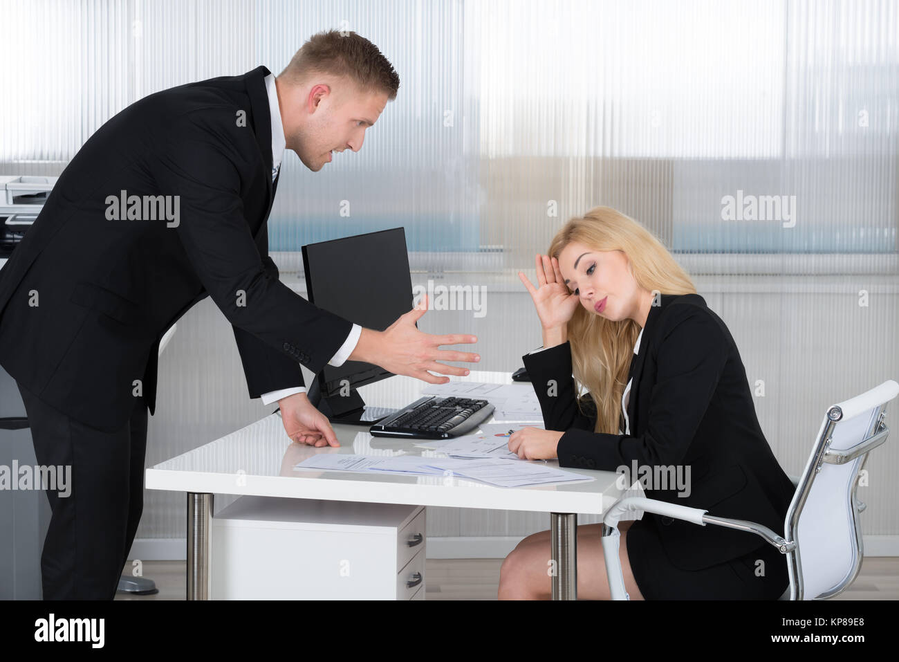 Boss Shouting At Employee Sitting At Desk - Stock Image