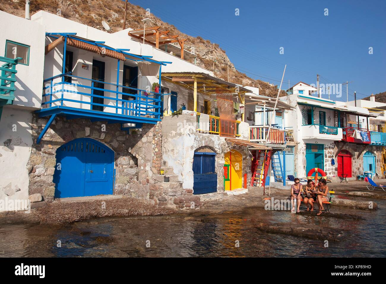 Tourists in front of the fisherman houses with boat shelters in Klima village, Milos, Cyclades Islands, Greek Islands, - Stock Image