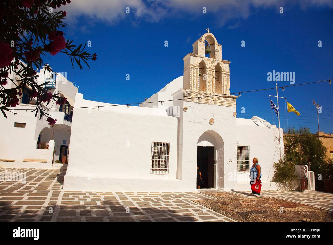 Local woman in front of the Church Of The Holy- Trinity, today the Ecclesiastical Museum of Milos, Adamas, Milos, - Stock Image