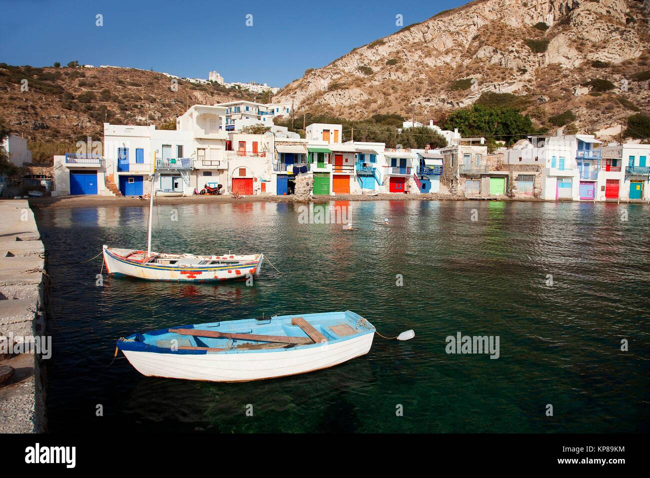 Local people swimming in the sea in front of the traditional fisherman houses with the impressive boat shelters - Stock Image