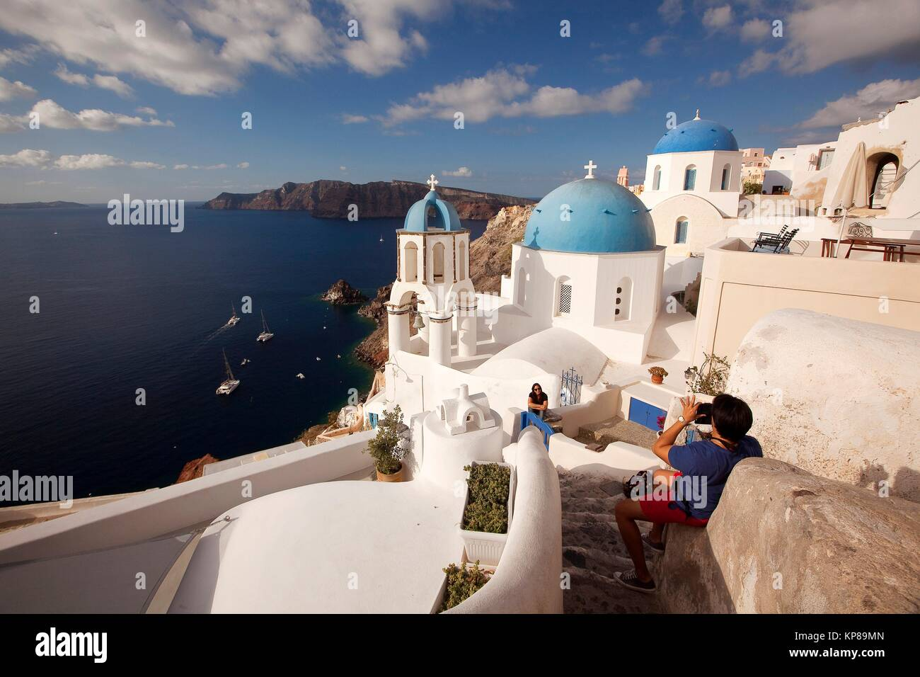 Tourists taking photos in front of the blue domed churches in Oia village, Santorini, Cyclades Islands, Greek Islands, Stock Photo
