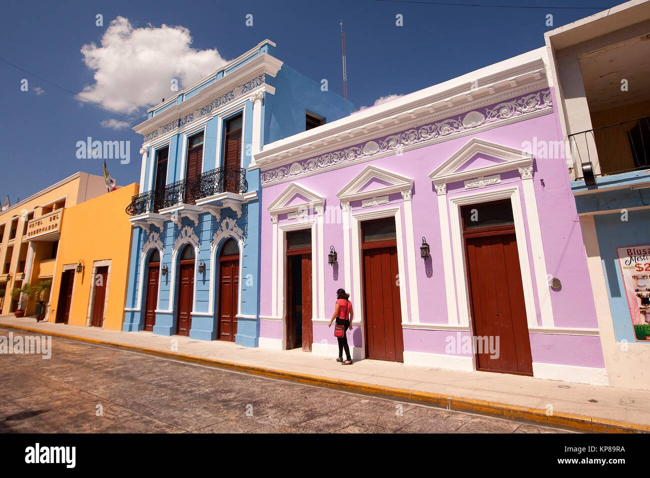 Woman walking in front of the colorful colonial buildings in