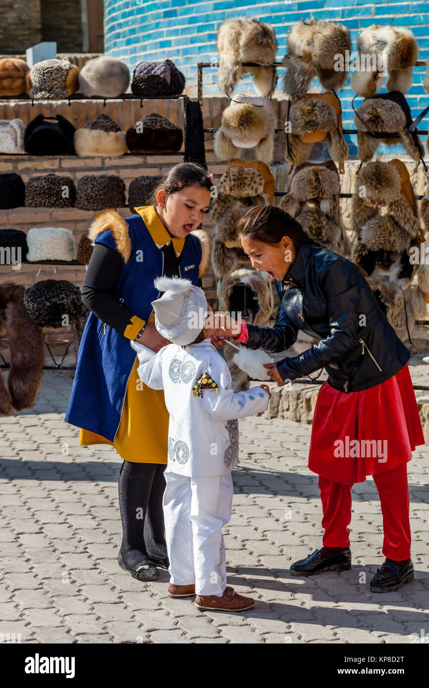 Two Sisters Feed Their Little Brother Candy Floss In The Old City Of Khiva, Uzbekistan - Stock Image