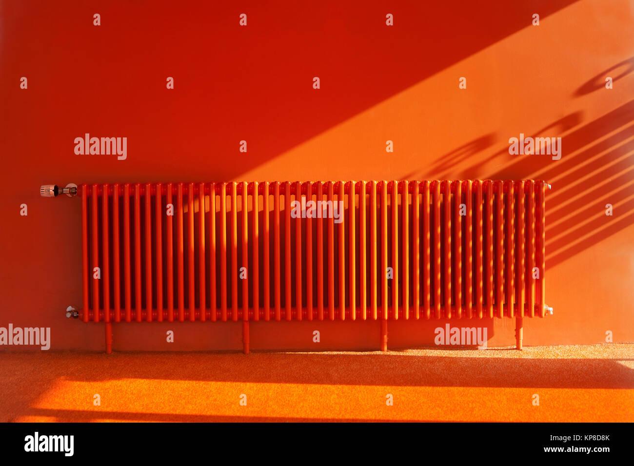 Orange radiator in a retro orange room - Stock Image