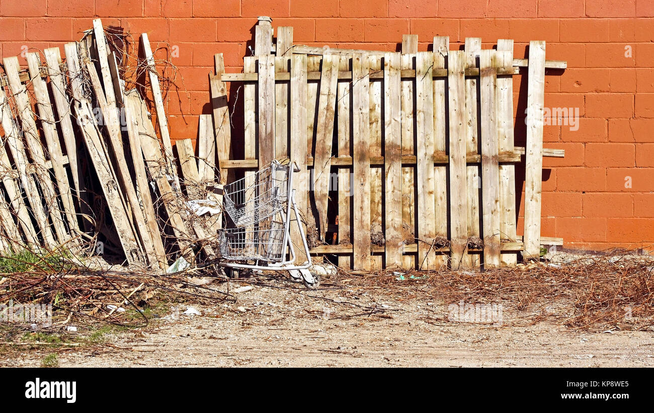 Old wooden fence and metal shopping cart that have been left as garbage at back of a building - Stock Image