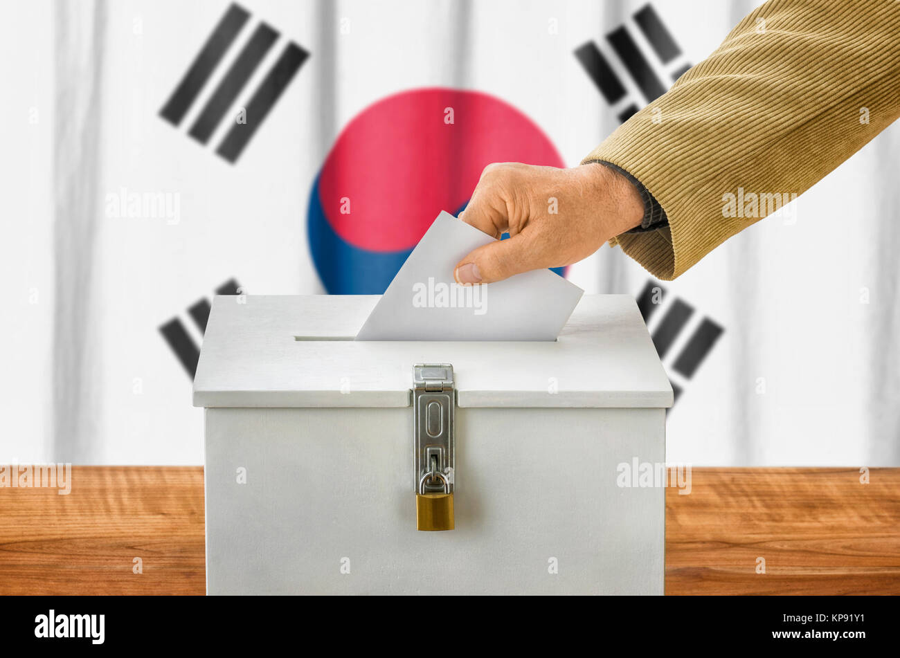 man putting ballot in the ballot box - south korea - Stock Image