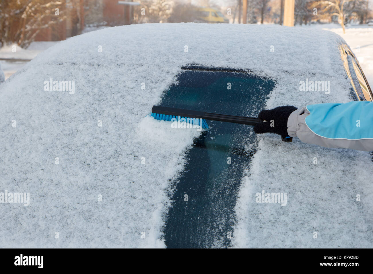 Clearing snow off a car - Stock Image