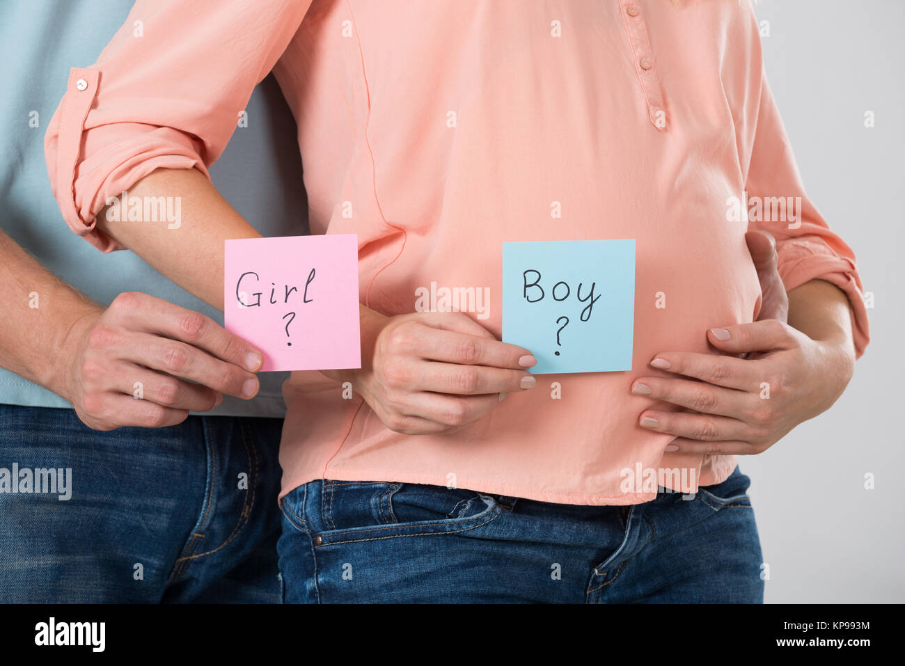 Expecting Couple Holding Paper With Girl And Boy Text - Stock Image