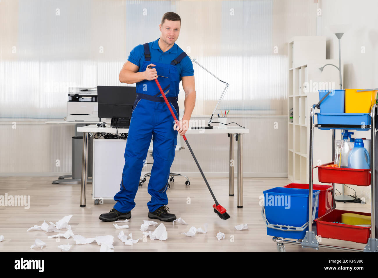 Janitor Cleaning Floor With Broom In Office - Stock Image