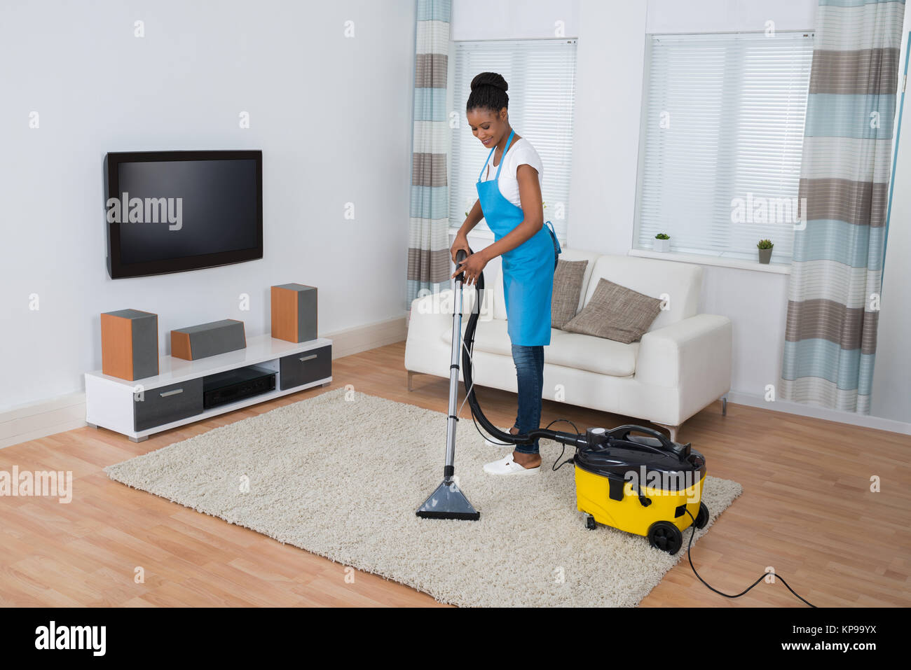 Woman Cleaning Carpet With Vacuum Cleaner - Stock Image