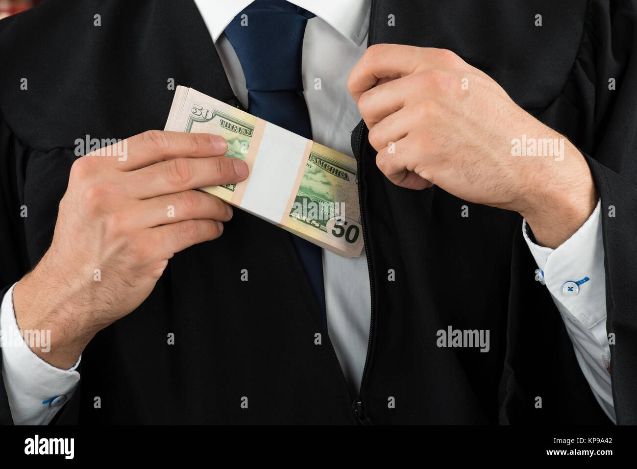 Judge Putting Dollar Bundle In Pocket Stock Photo