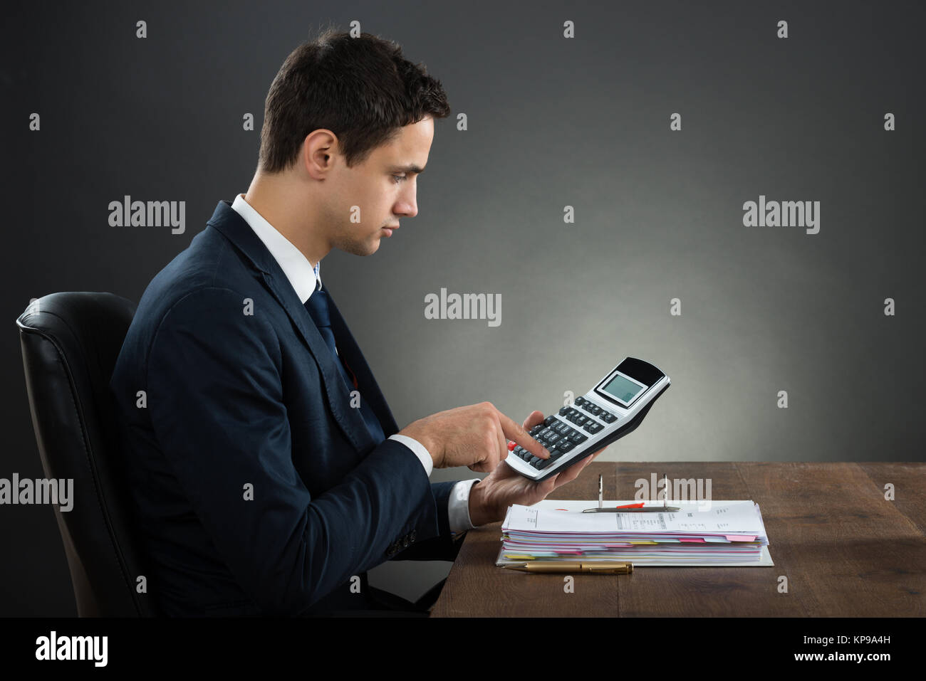 Businessman Using Calculator While Checking Invoice At Desk Stock Photo