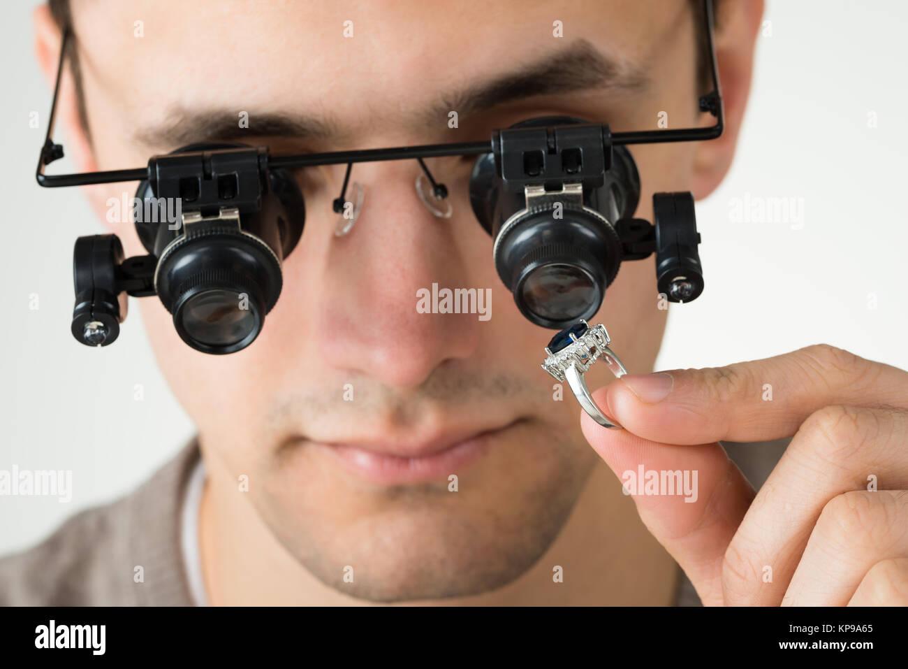 Jeweler Examining Diamond Ring With Magnifying Loupe Stock Photo