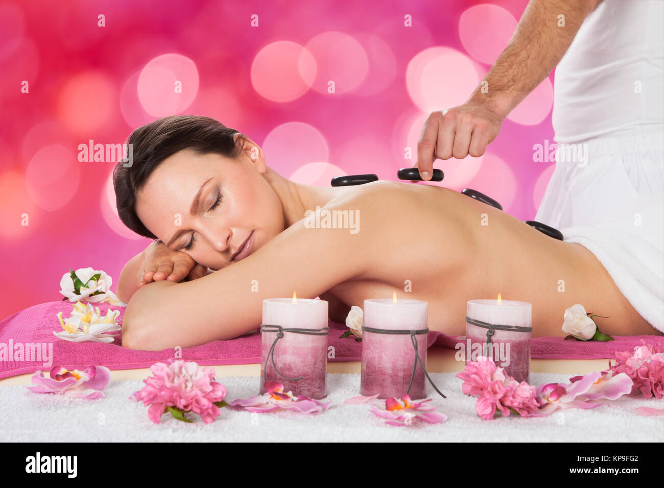 Relaxed Woman Receiving Hot Stone Therapy - Stock Image