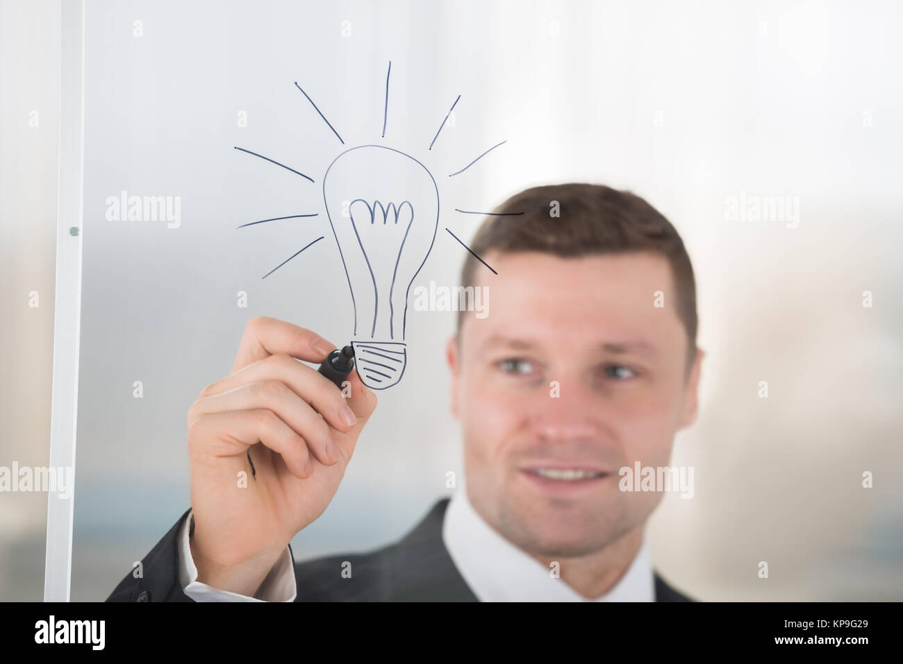 Businessman Drawing Lightbulb On Glass Wall In Office - Stock Image