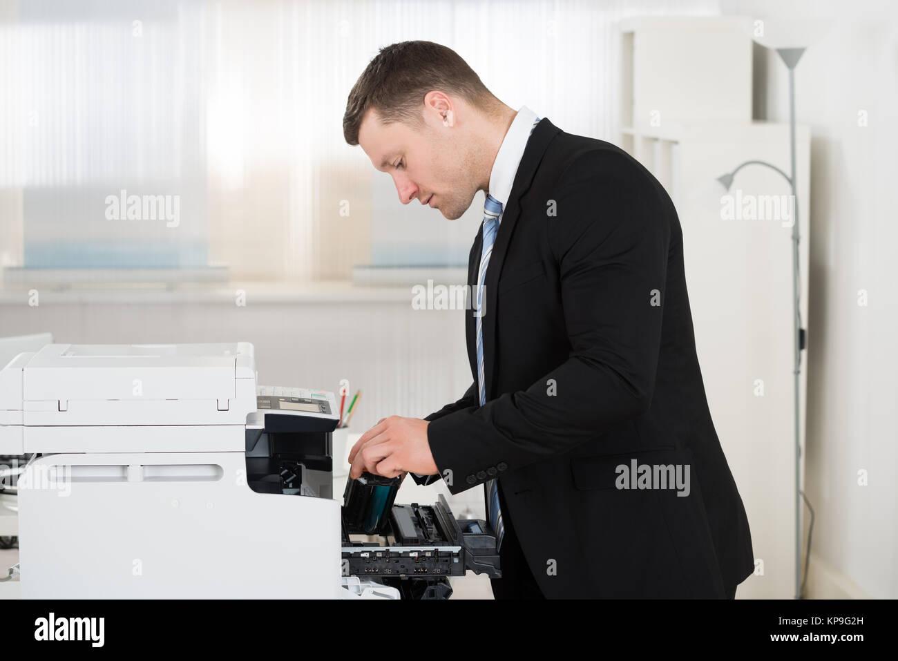 Businessman Adjusting Cartridge In Photocopy Machine - Stock Image