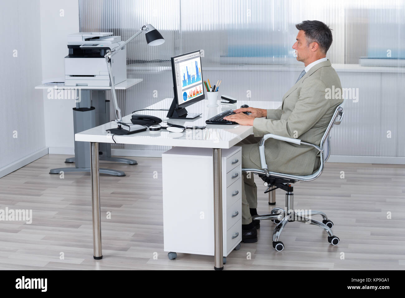 Businessman Using Computer At Desk In Office - Stock Image