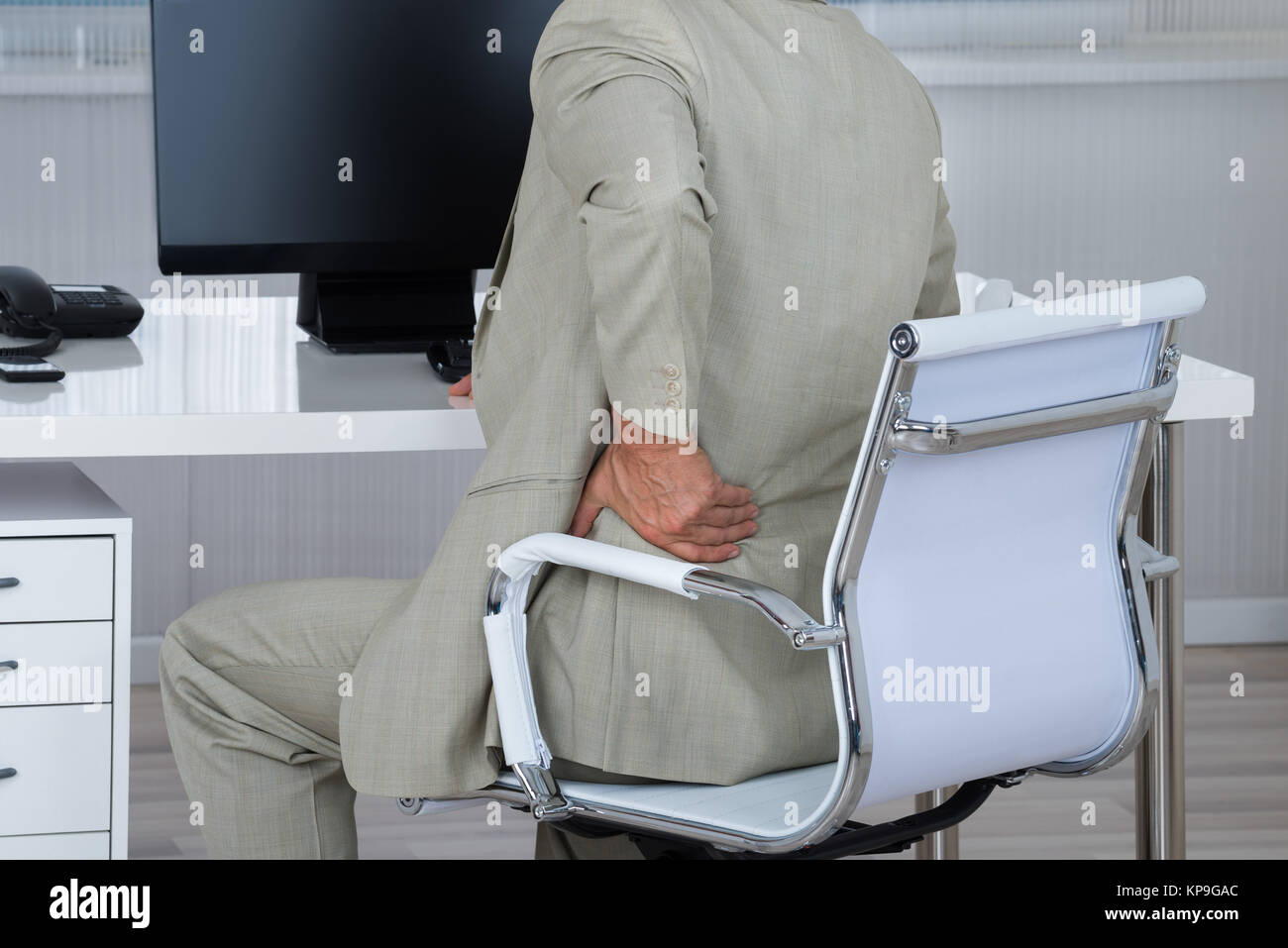 Businessman Suffering From Backache While Sitting On Chair - Stock Image