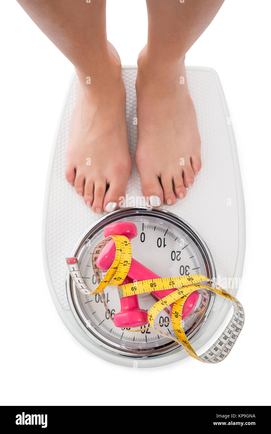 Woman Stepping On Weight Scale With Dumbbells And Tape Measure - Stock Image