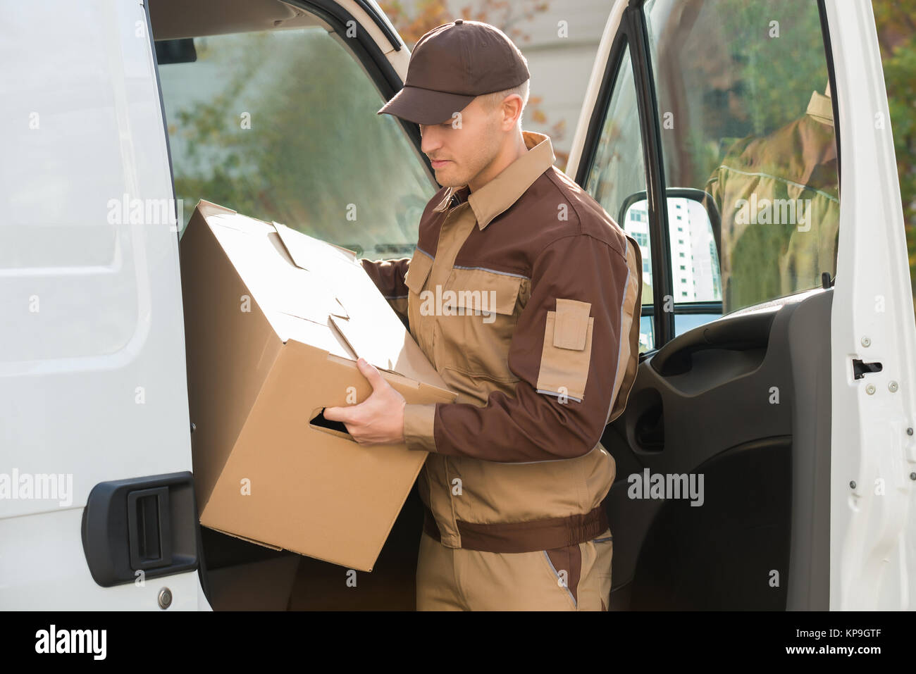 Delivery Man Removing Cardboard Box From Truck - Stock Image