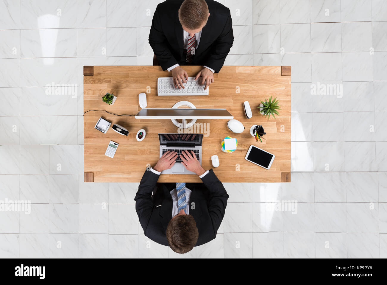 Businessmen Using Laptop And Computer At Desk In Office - Stock Image