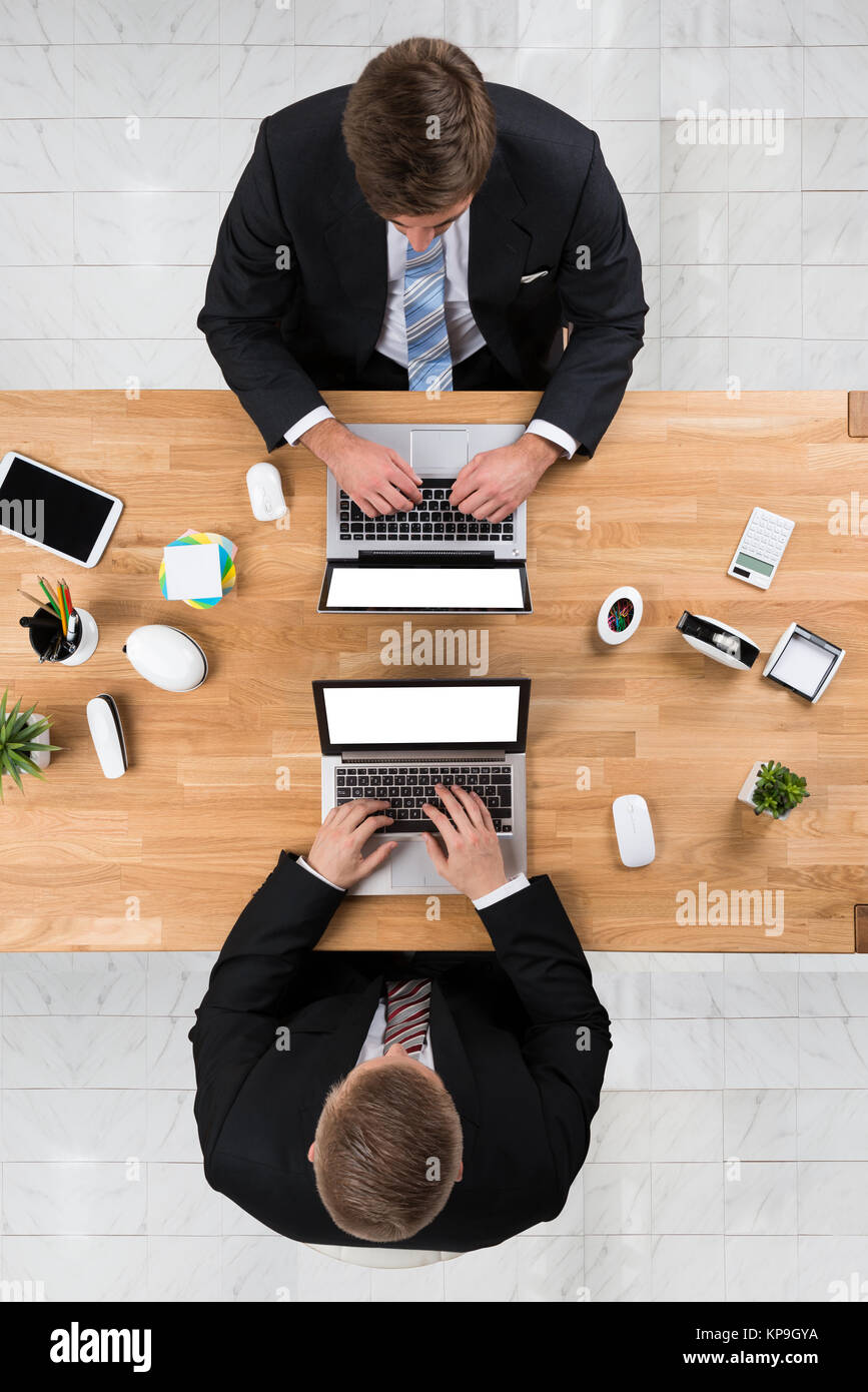 Businessmen Using Laptops At Desk In Office - Stock Image