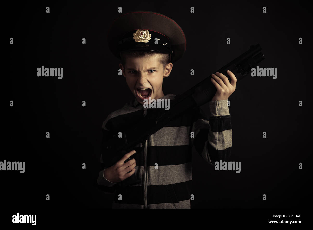 Screaming Boy with Police Hat Holding Rifle - Stock Image