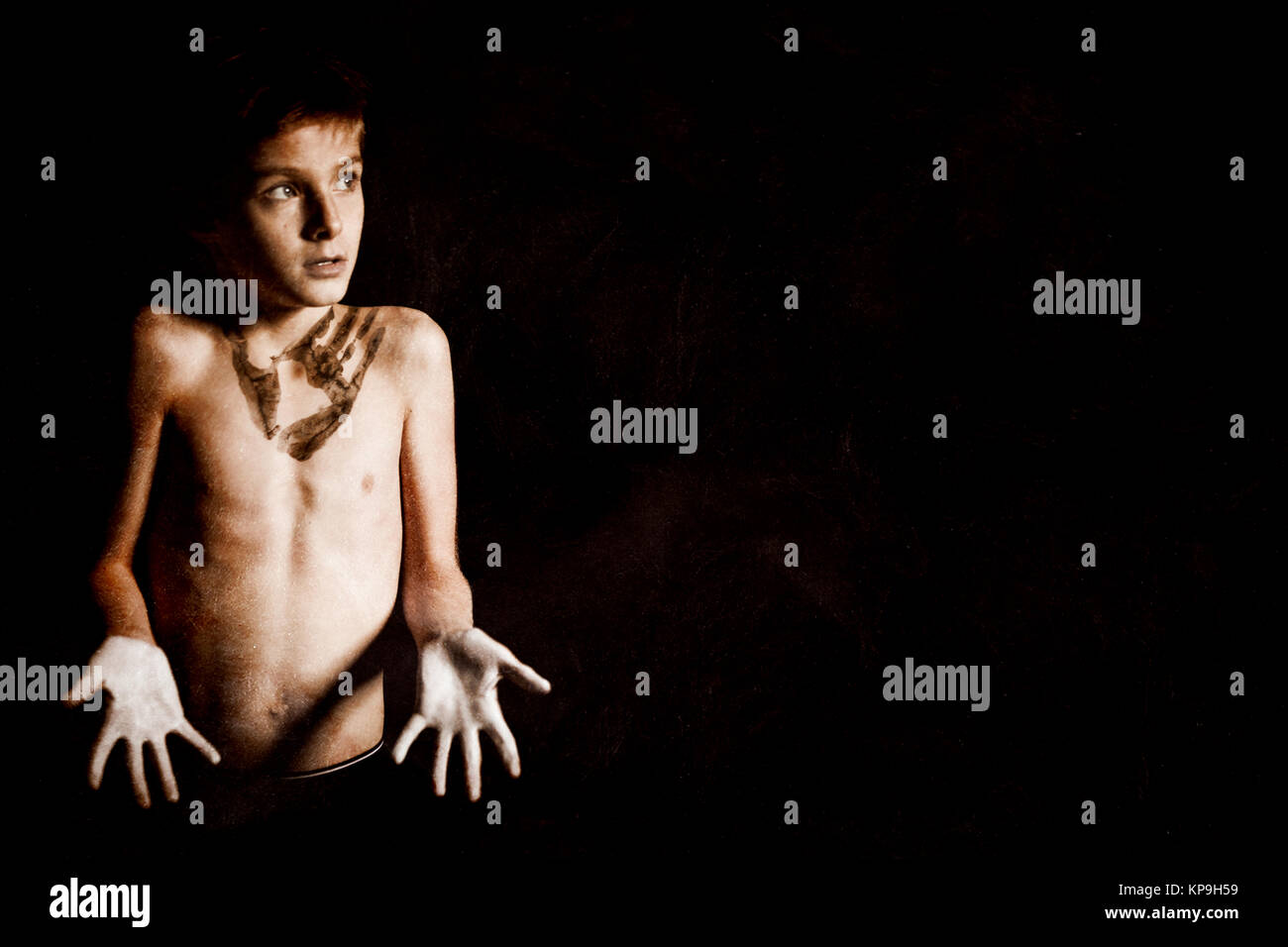 Clueless Shirtless Boy on Black with Copy Space - Stock Image