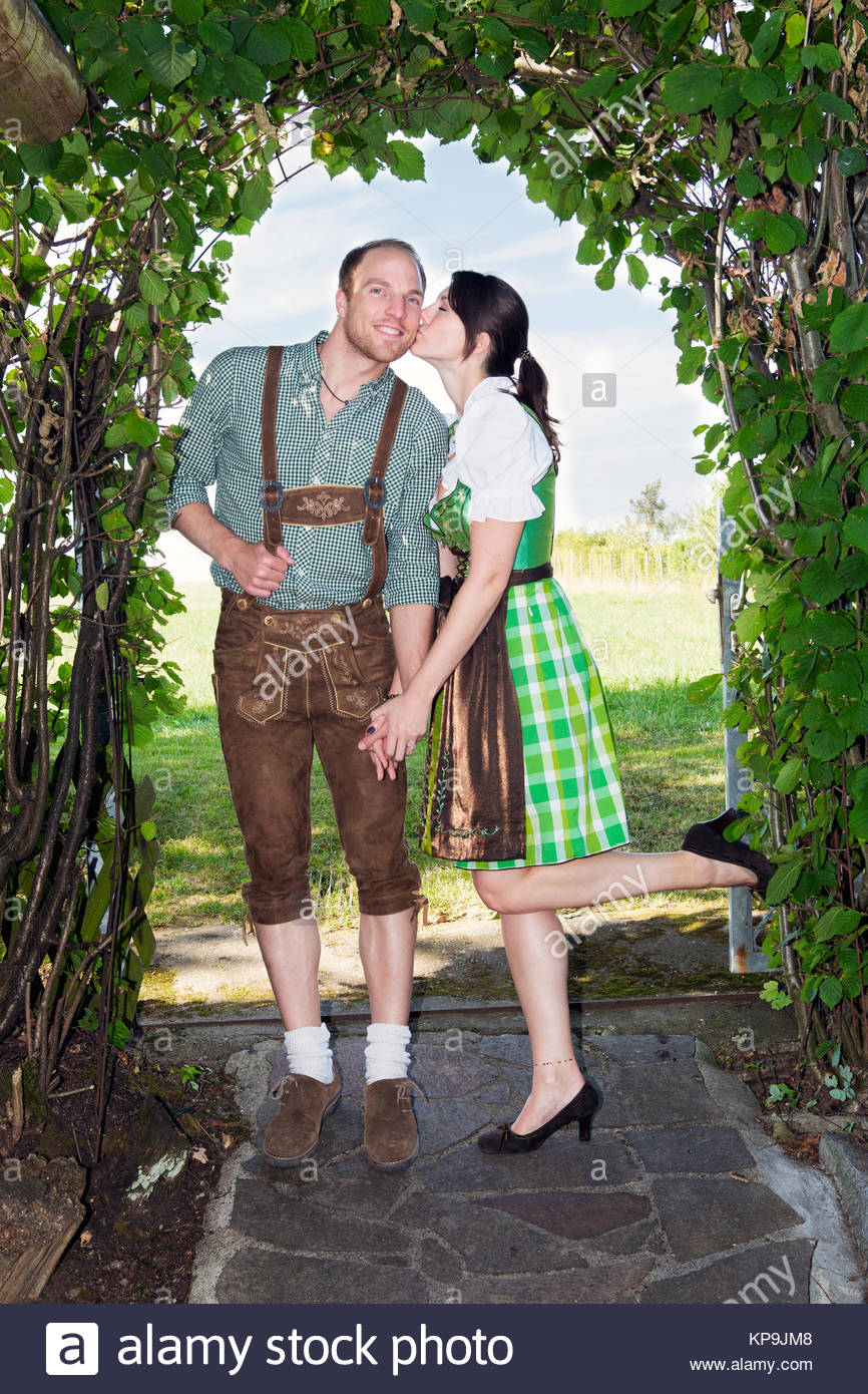 bavarian girl giving her boyfriend a kiss - Stock Image
