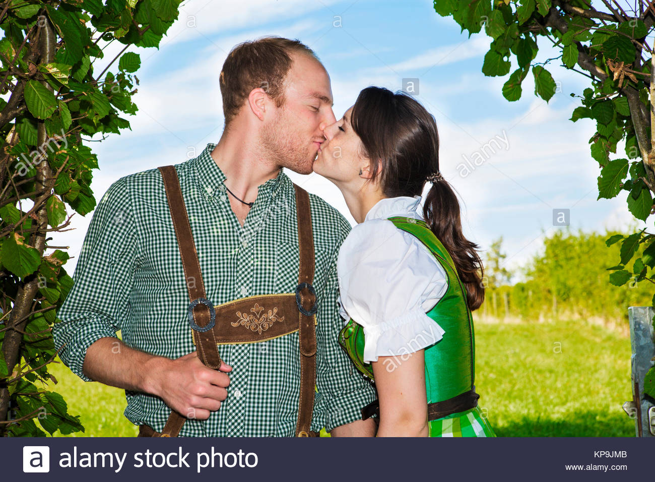 bavarian couple kissing each other - Stock Image