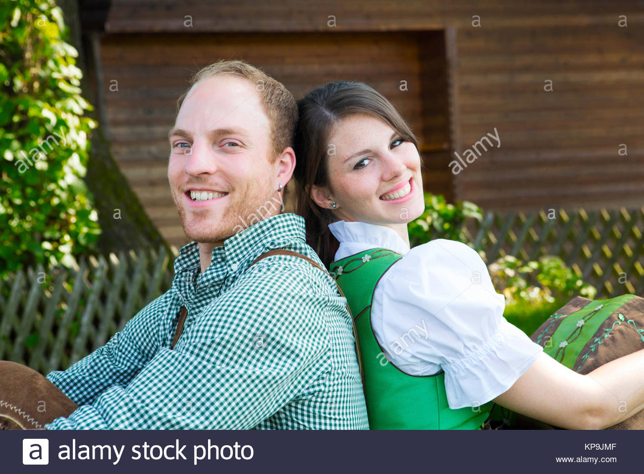 bavarian couple leaning against each other - Stock Image