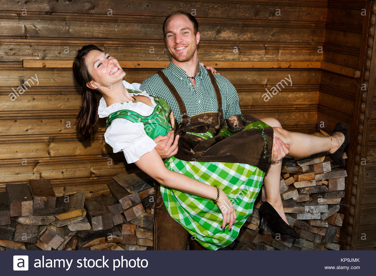 bavarian man holding his girlfriend - Stock Image