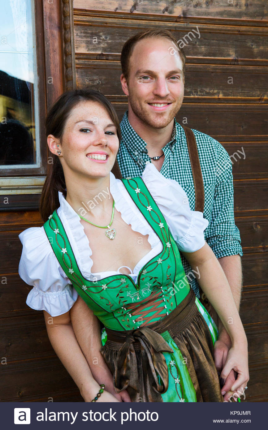 bavarian couple standing in front of a wooden house - Stock Image