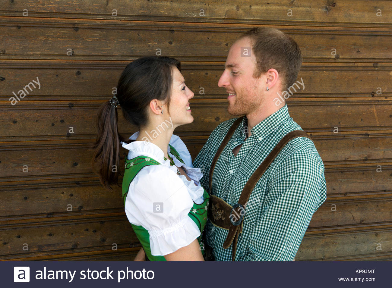 couple in traditional bavarian clothes hugging each other - Stock Image