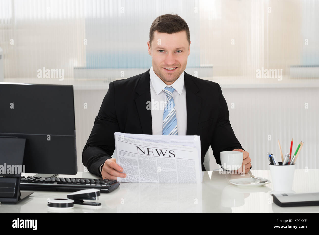Businessman Holding Newspaper And Coffee Cup At Desk - Stock Image