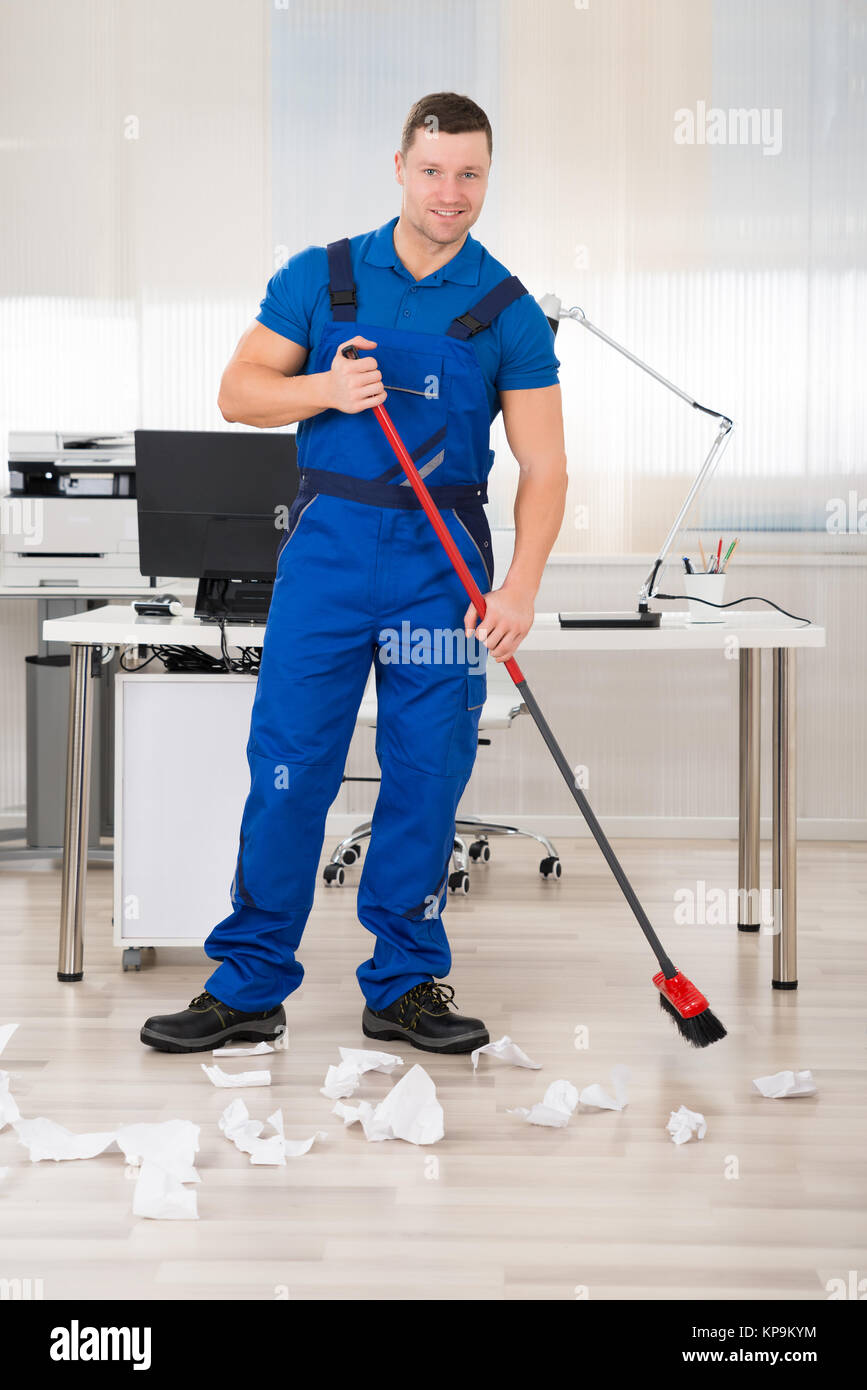 Smiling Janitor Holding Broom In Office - Stock Image