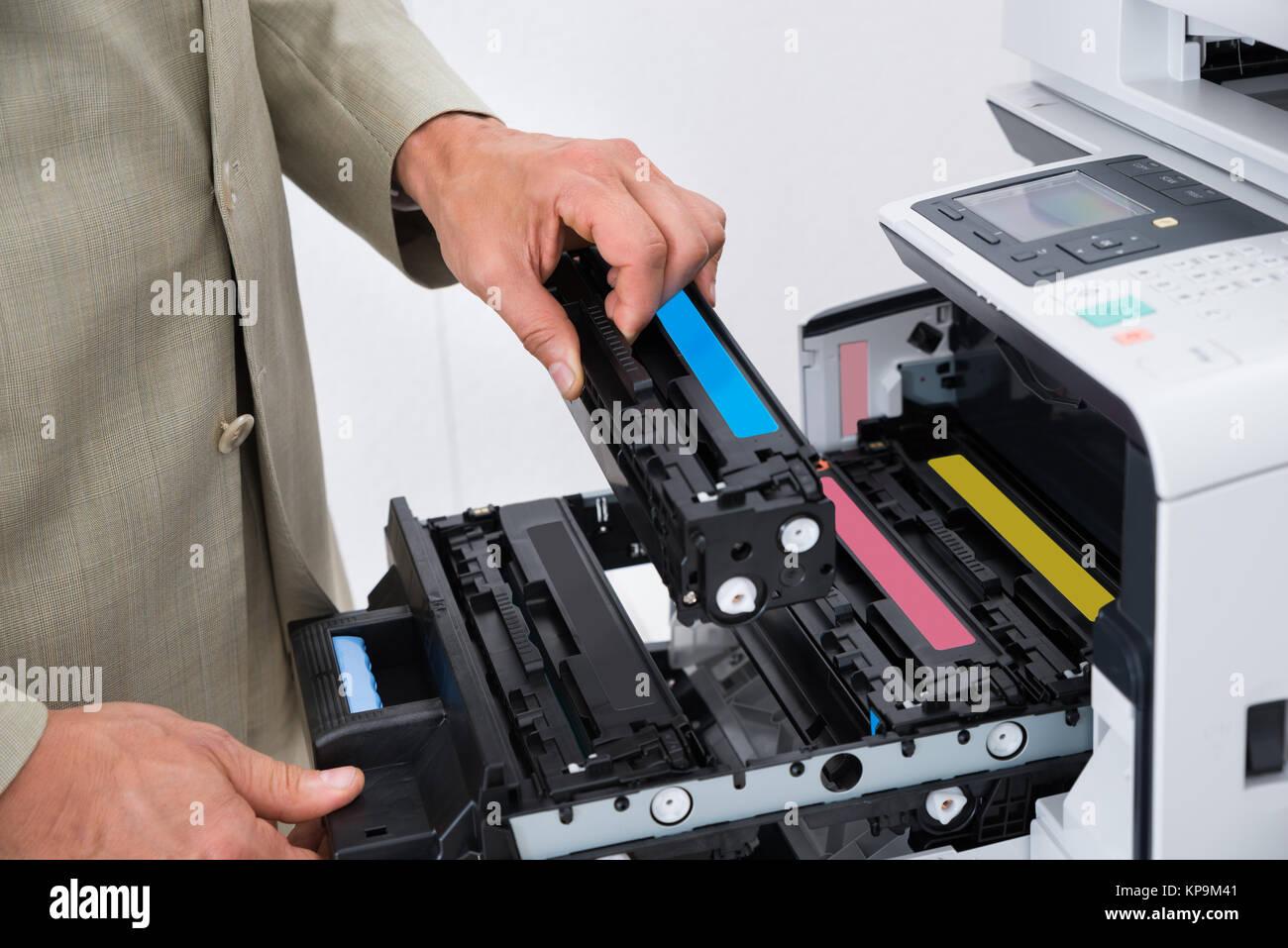 Businessman Fixing Cartridge In Photocopy Machine - Stock Image