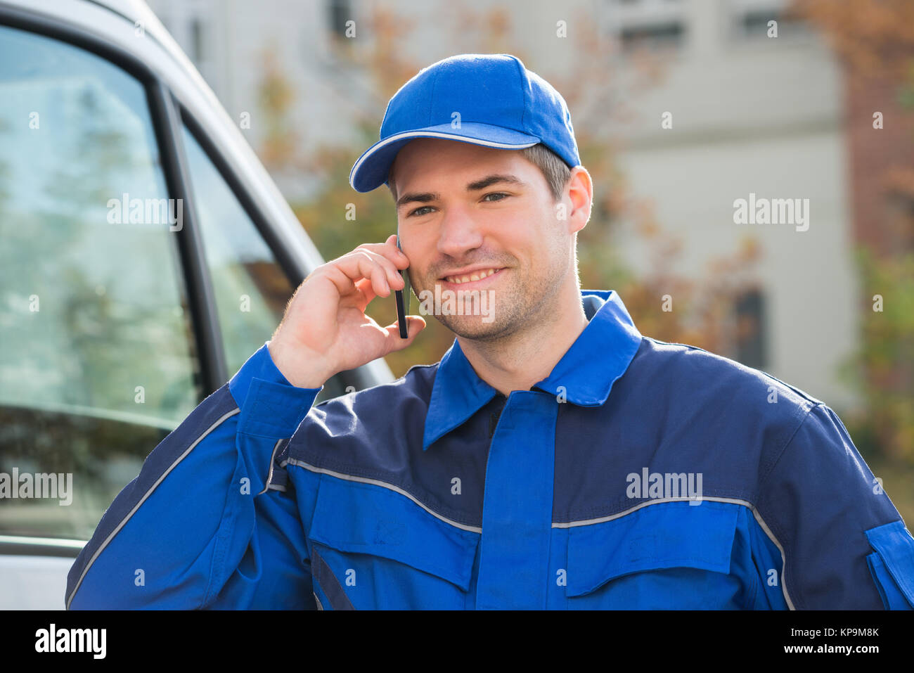 Delivery Man In Uniform Using Mobile Phone - Stock Image