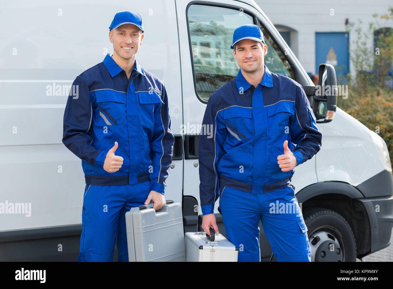 Happy Technicians Showing Thumbsup Against Truck - Stock Image
