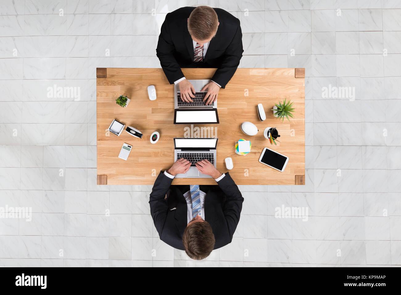Businessmen Using Laptops At Desk In Office Stock Photo