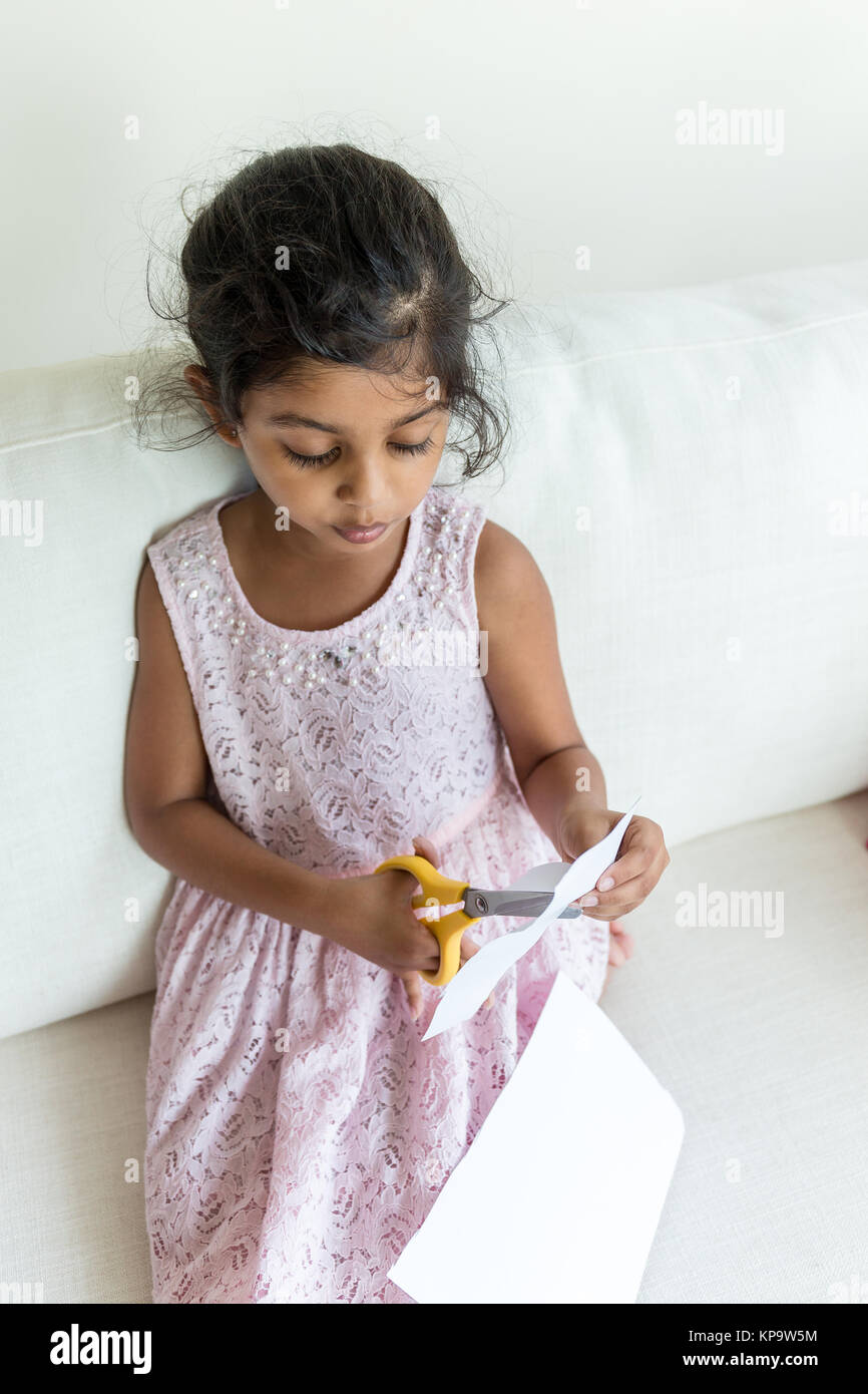 Young girl cutting the paper - Stock Image