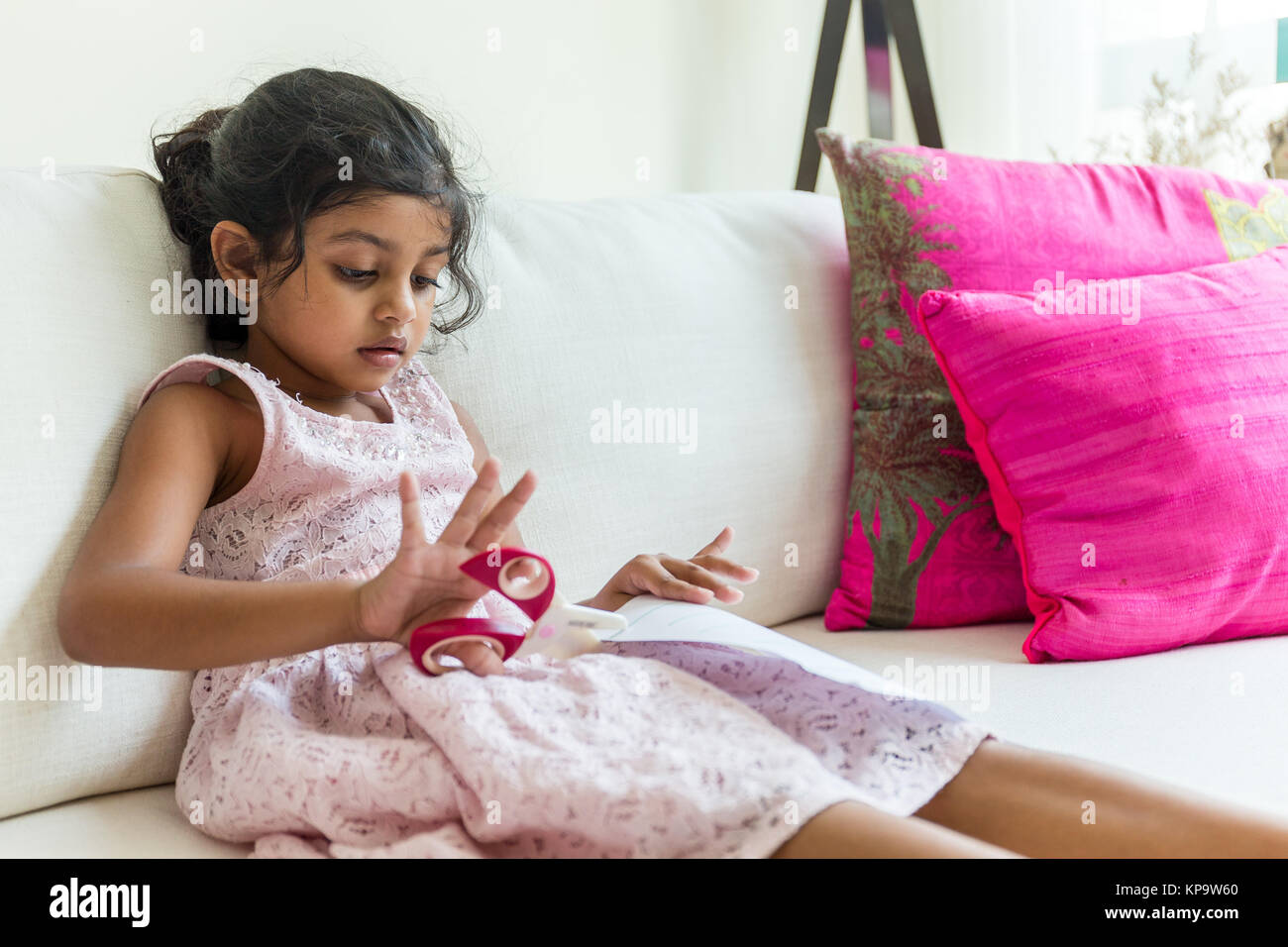 Indian Young girl learn to use the scissor for cutting paper - Stock Image