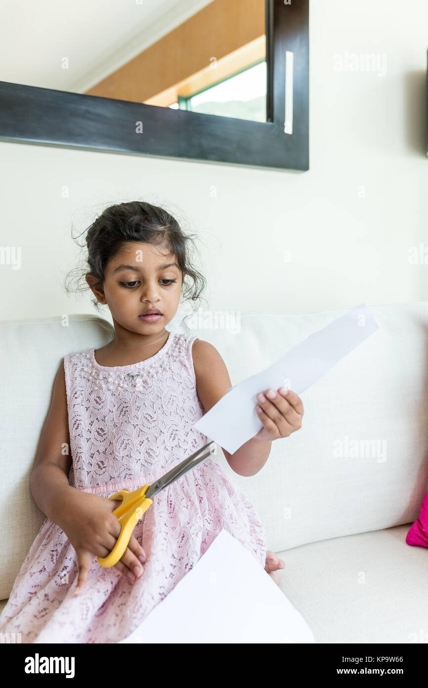 Little girl use the scissor for cutting paper - Stock Image