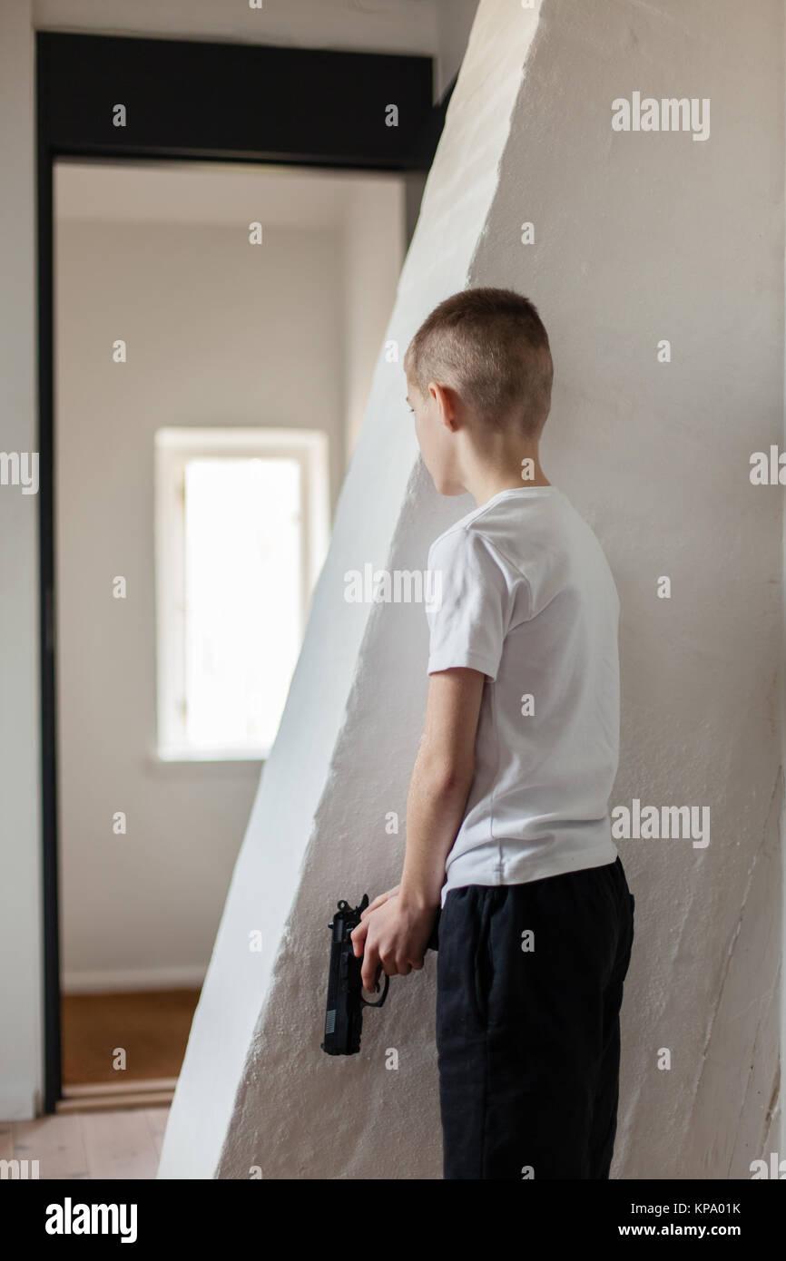 Boy Holding Gun Waiting Someone Behind the Wall - Stock Image