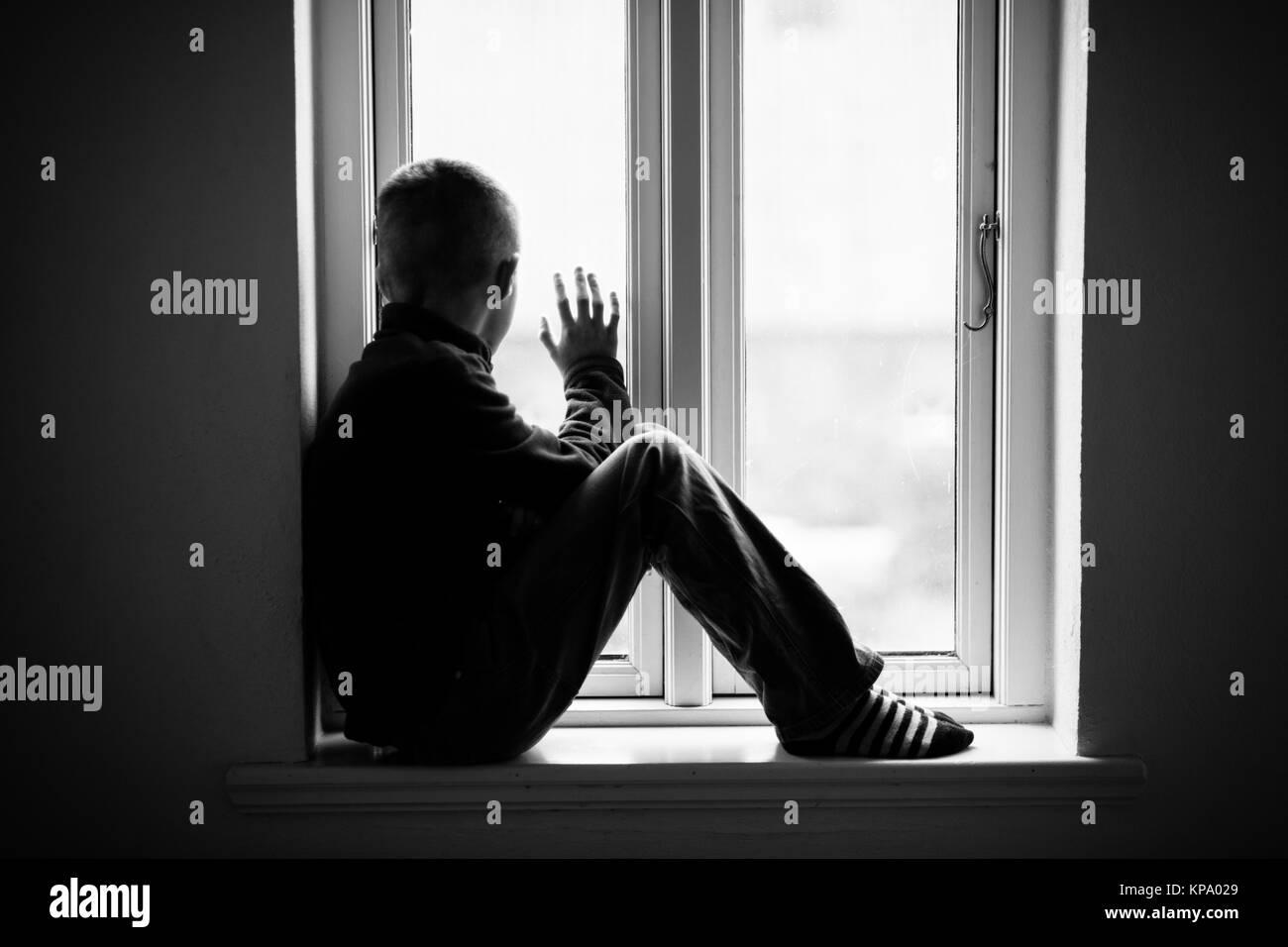 Boy Sitting on Windowsill While Looking Outside - Stock Image